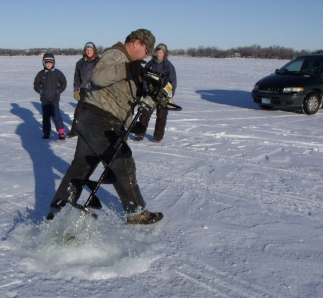 Don digging one of the ice fishing holes.  See the water come splashing out!