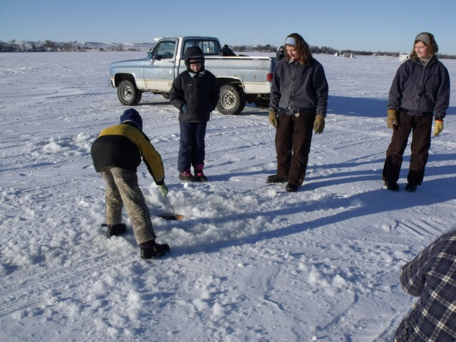 Mario cleans out a freshly dug ice fishing hole.