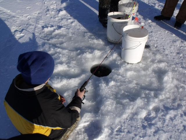 A good view of what it looks like when a person fishes on ice.
