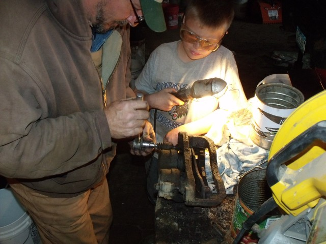 Father and son, fixing the brakes....what a great place here on the farm for boys to learn hands on.