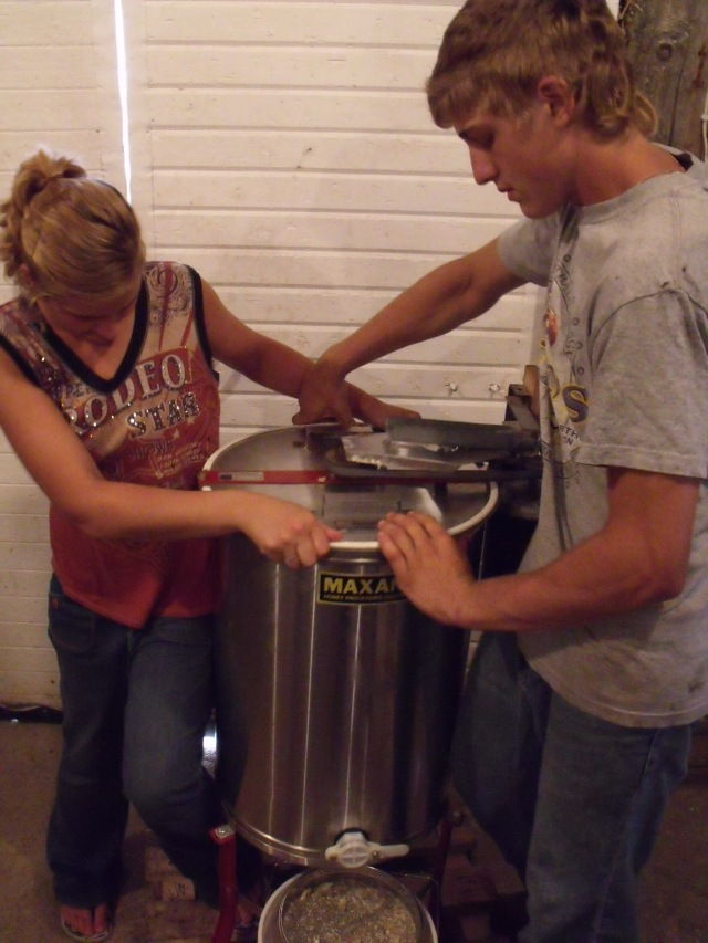 Maggie and Caleb steady and operate the honey extractor.