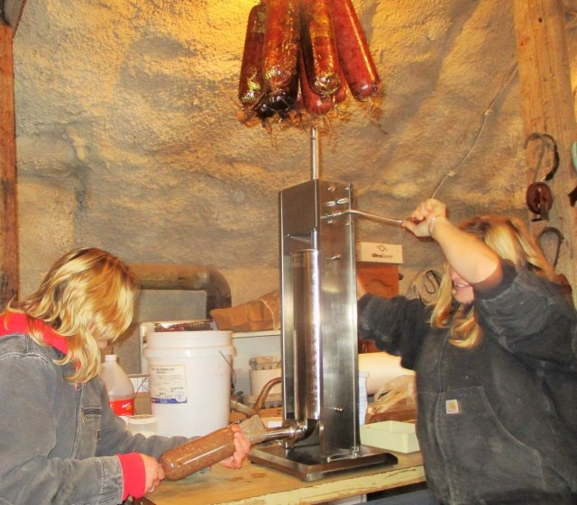 Silvana and Marisa stuffing sausages. On top hanging are some of the smoked sausages.